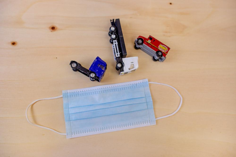 Blauer medizinischer Mund-Nasen-Schutz und drei Spielzeug LKWs Logistik