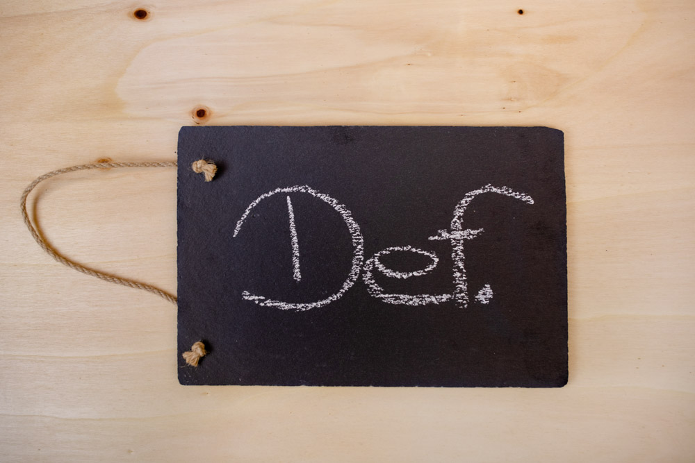 Schiefertafel mit Kreide Schriftzug Def. für Definition Interim Management