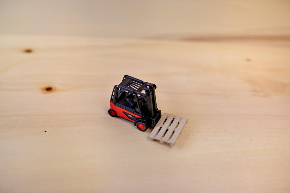 Spielzeug Gabelstapler mit kleiner Holzpalette auf Holzuntergrund