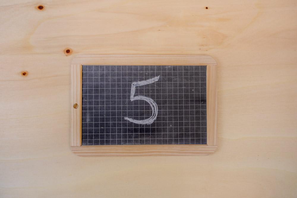 Kleine Schultafel mit Kreide Schriftzug 5 auf Holzuntergrund
