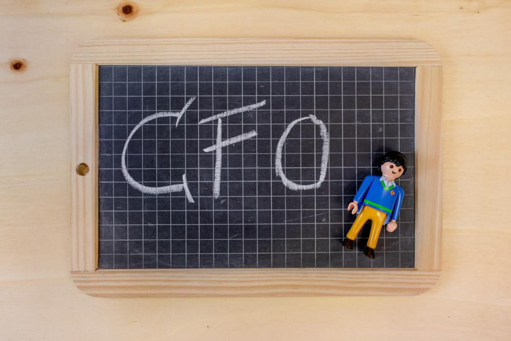 Kleine Holztafel mit Kreise Schriftzug CFO und einer kleinen männlichen Spielfigur darunter