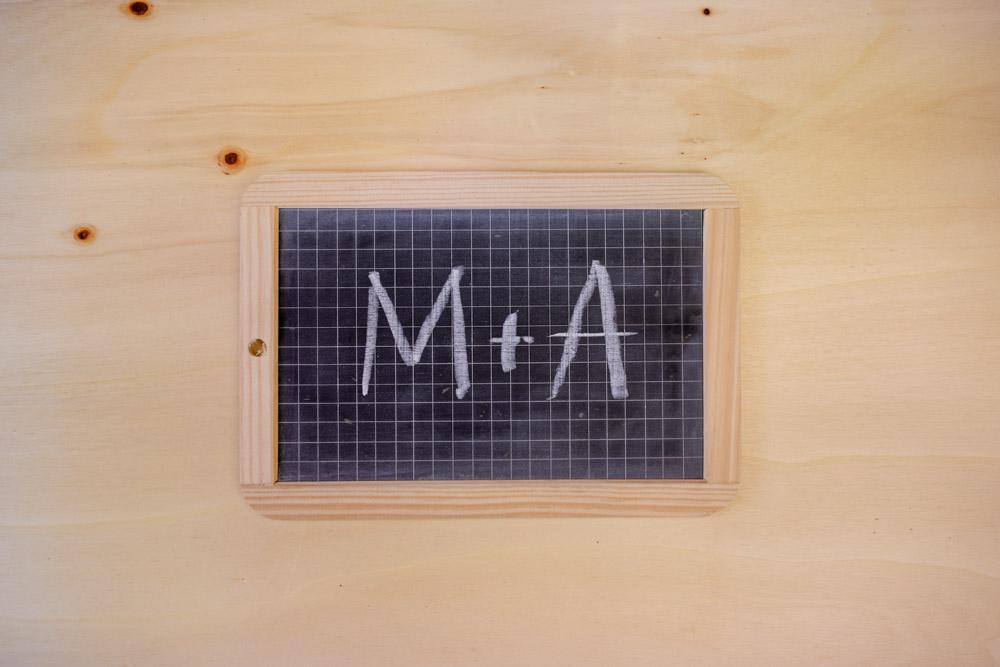 Kleine Schultafel mit Schriftzug M&A auf Holzuntergrund