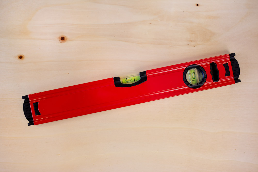 Rote Wasserwaage auf Holzuntergrund leicht schief liegend