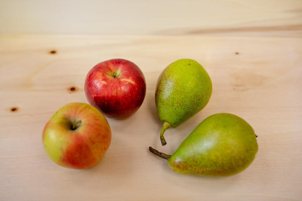 Zwei rot grüne Äpfel, zwei grüne Birnen liegen nebeneinander