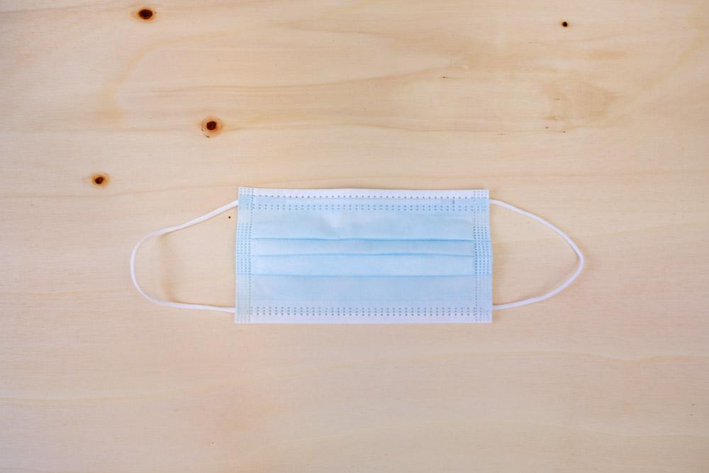 Blauer medizinischer Mund-Nasen-Schutz auf Holzuntergrund