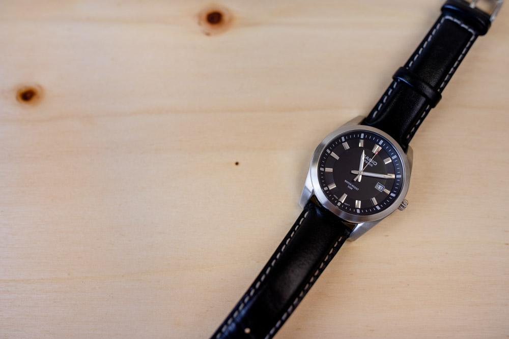 Armbanduhr schwarz silber mit Uhrzeit 11.11 Uhr auf Holzuntergrund