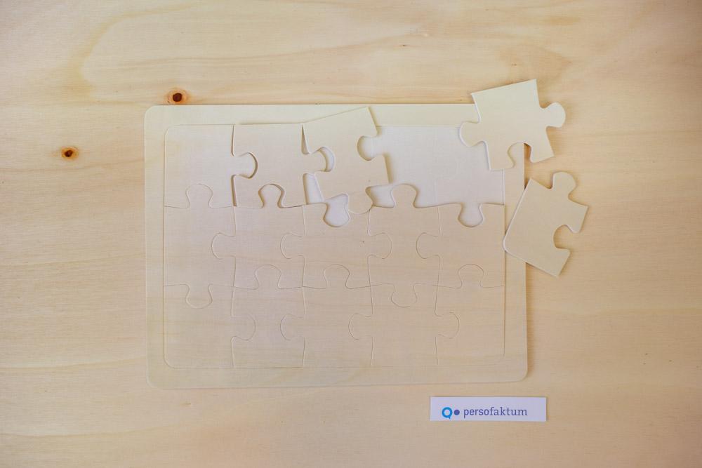 Holzpuzzle mit losen Teilen auf Holzuntergrund