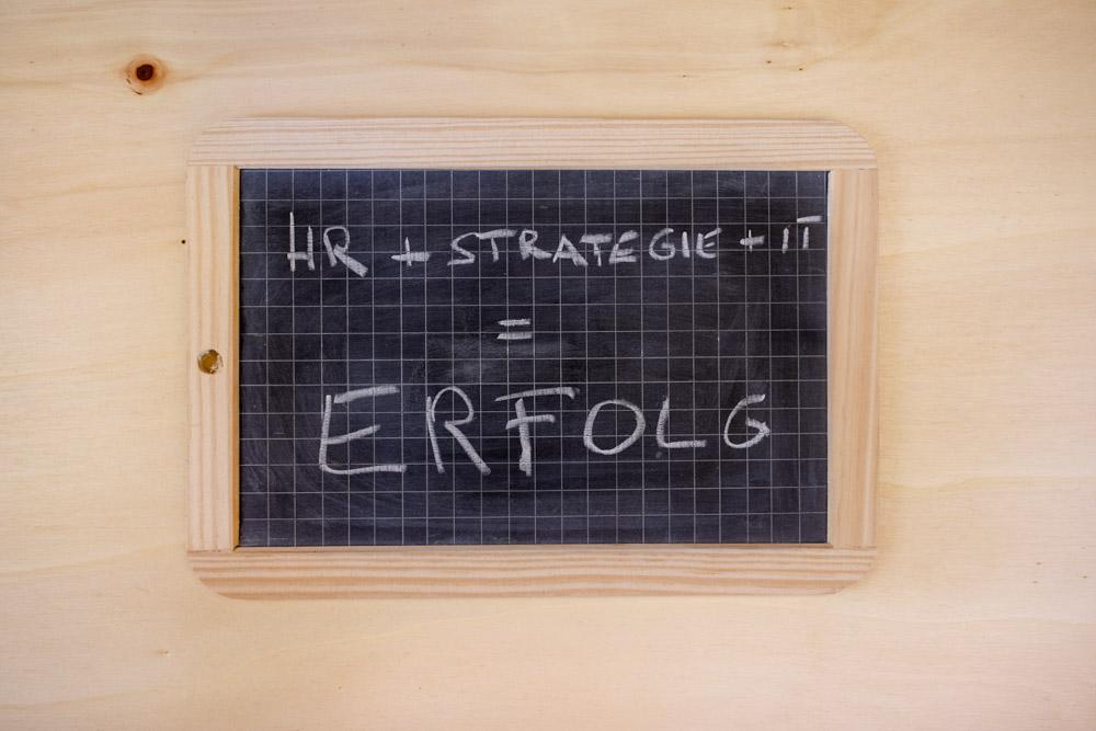 Kleine Schultafel mit Formel HR + Strategie + IT = Erfolg auf Holzuntergrund