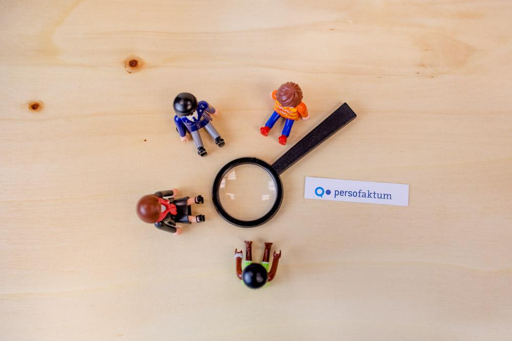 Spielzeugfiguren sitzen im Kreis um eine Lupe auf einem Holzuntergrund plus ein persofaktum Logo