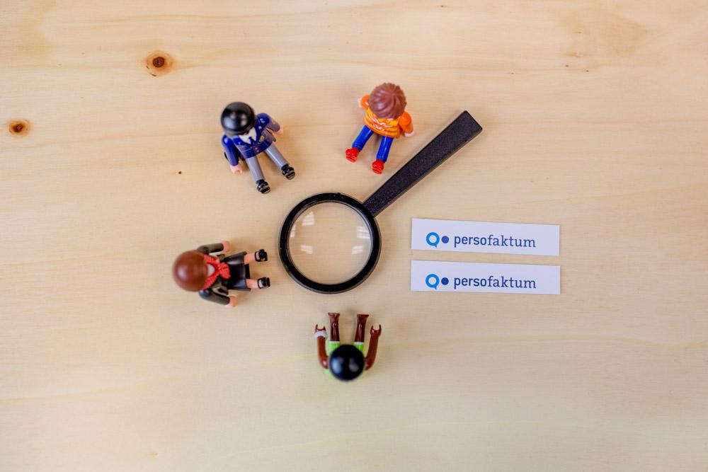 Spielzeugfiguren sitzen im Kreis um eine Lupe auf einem Holzuntergrund plus zwei persofaktum Logos