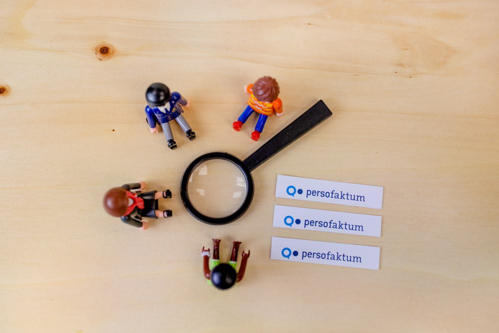 Spielzeugfiguren sitzen im Kreis um eine Lupe auf einem Holzuntergrund plus drei persofaktum Logos