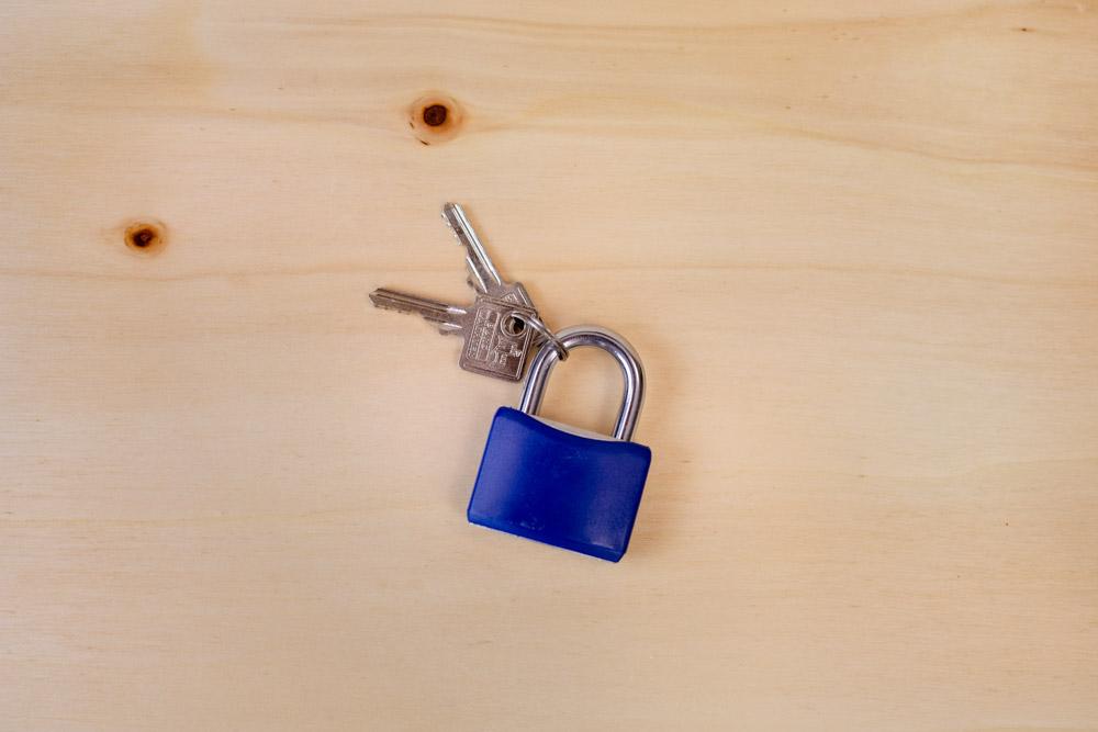 Sie sehen ein verschlossenes, blaues Vorhängeschloss mit Schlüsseln auf einem Holzuntergrund um Verschwiegenheit bei Interim Personalleitung zu unterstreichen.