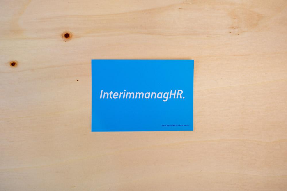 Blaue Postkarte auf Holzuntergrund Schriftzug Interim Manager HR