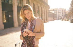 ragazza bionda usa lo smartphone in strada