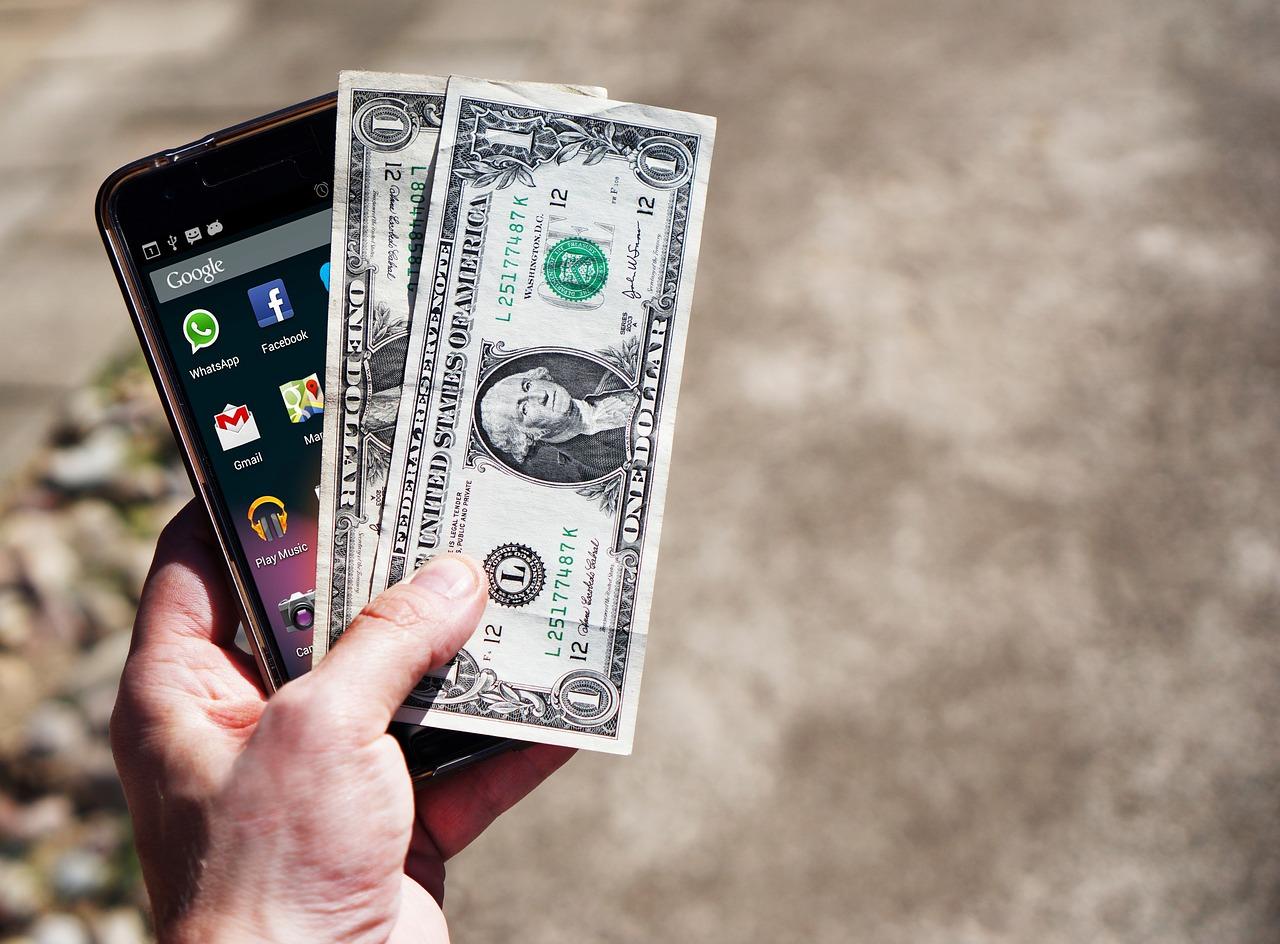 app per dividere spese - Mano con soldi e smartphone