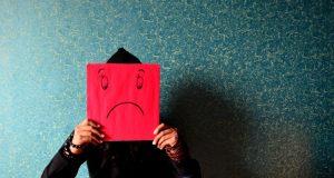 persona triste con cartello