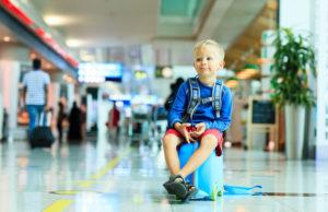 aeroporto bambino seduto sulla valigia