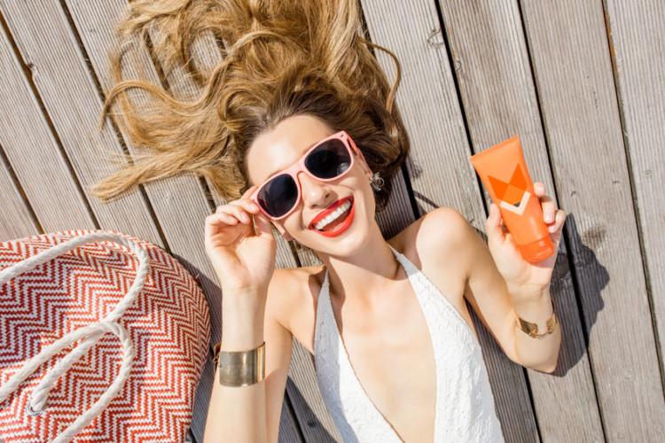 donna bionda con occhiali da sola e crema solare in mano
