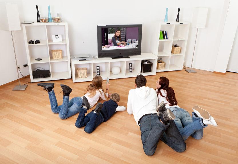 famiglia sdraiata sul pavimento mentre guarda la tv