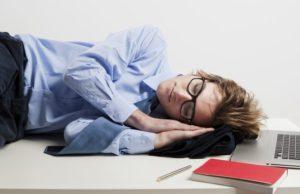 giovane impiegato bancario dorme sulla scrivania