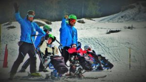 maestri di sci con disabili sulla neve