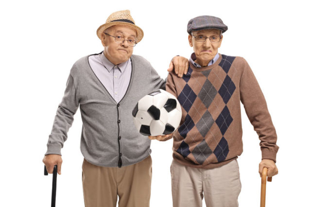 Disappointed seniors holding a deflated football Sky calcio recesso
