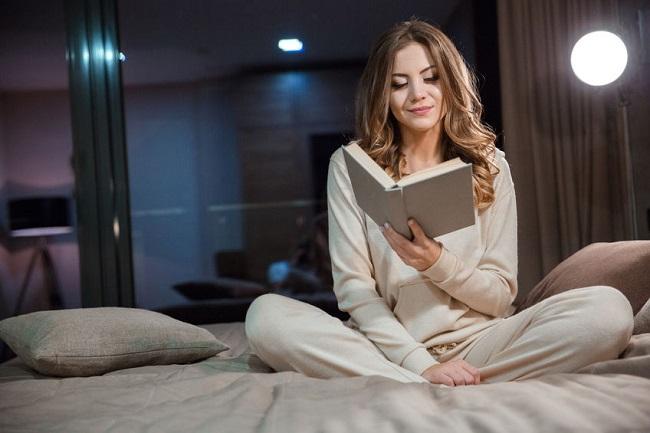 illuminazione casa donna che legge con la lampada