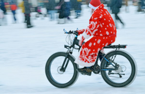 Un uom vestito da babbo natale che utilizza l'e-bike
