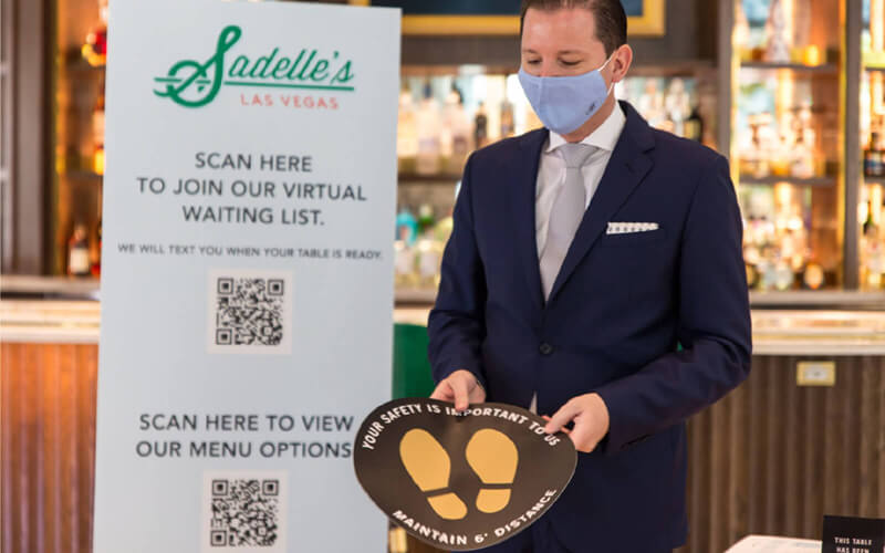 Sadelle's display sign with QR Codes for menu options and to join the waiting list
