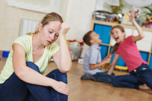 Die verzweifelte Mutter auf dem Bild, wünscht sich wegen ihrer streitenden Kinder, eine Supernanny