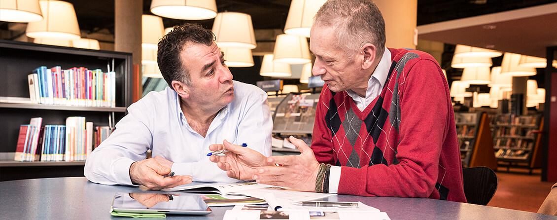 Man helpt andere man met taal in een bibliotheek