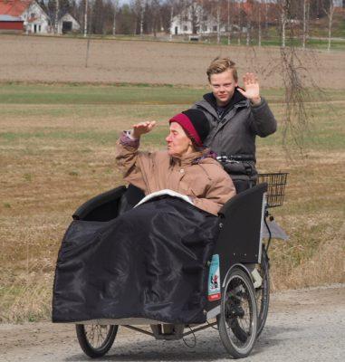 poika ajaa riksapyörää, jossa vanhus ihailee maisemaa
