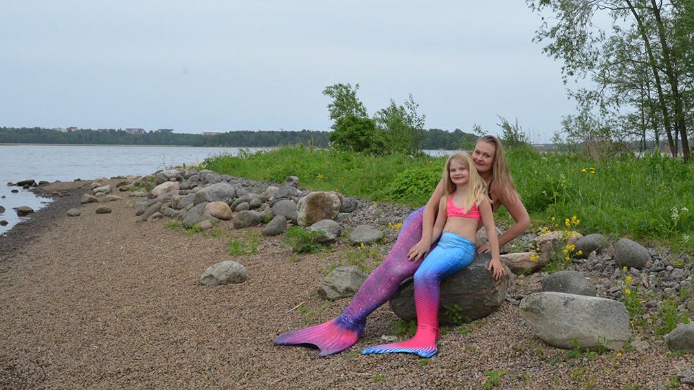 Ada ja Ani-Jatta istuvat rantakivillä. Merenneitopuku tekee uimarista todellisen merenneidon.