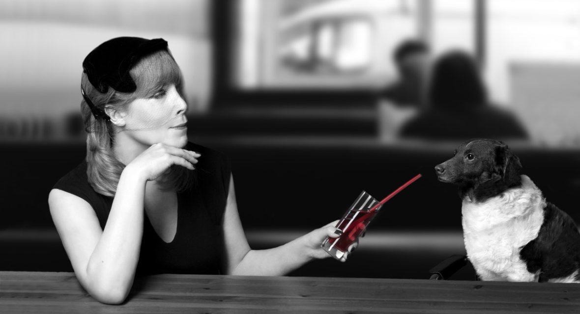 Frau sitzt mit Hund an der Bar und trinkt einen Cocktail