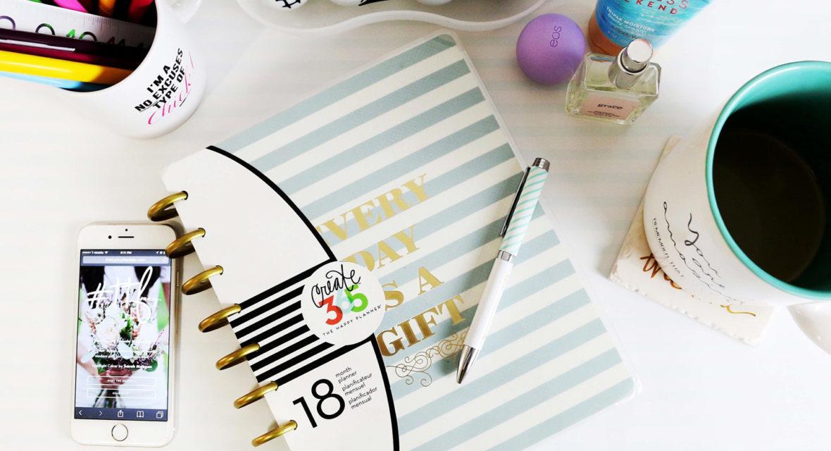 Schreibtisch mit Stiften, Notizbuch, Handy und Kaffeetasse.