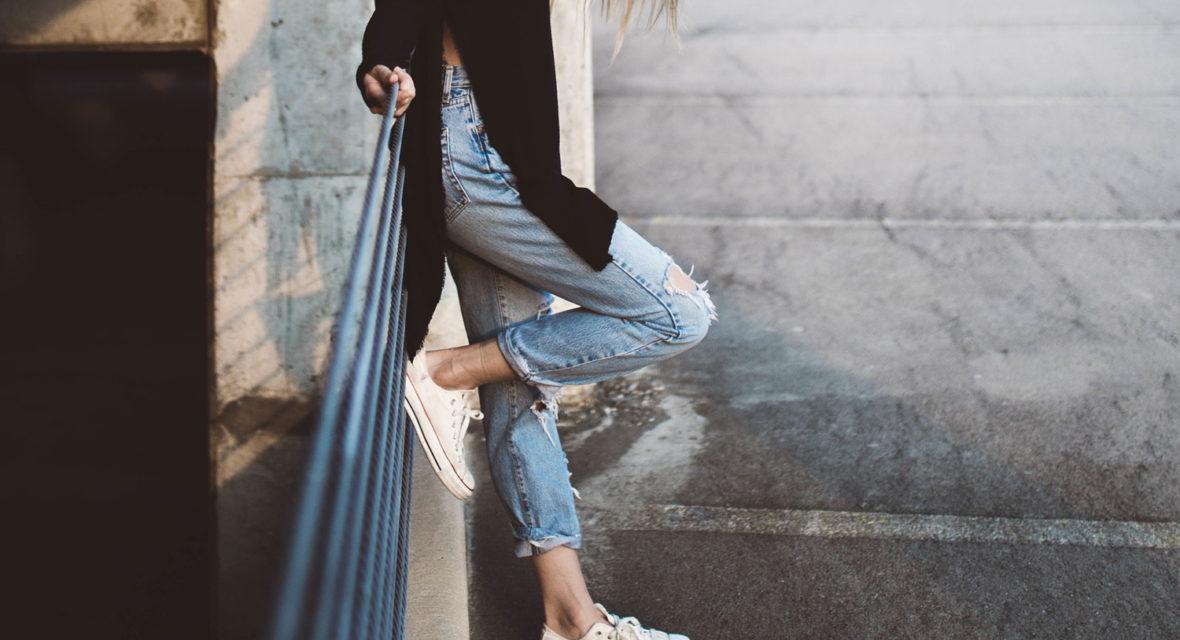 Frau in Jeans lehnt an Wand.