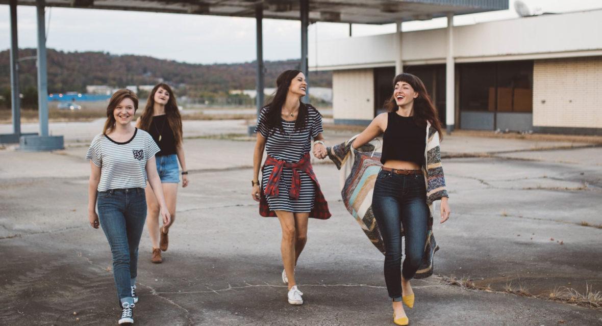 Mädchen laufen neben altem Gebäude.