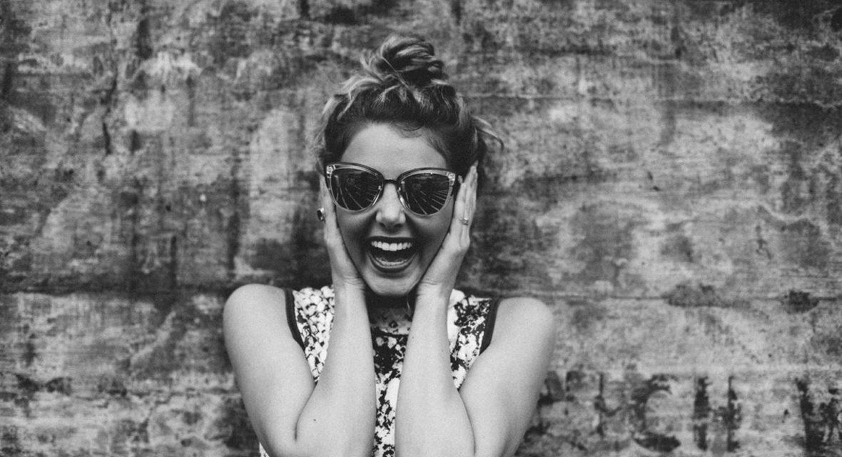 Frauch hat sonnenbrille auf und lacht.