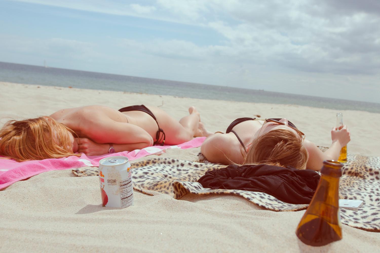 Zwei Frauen liegen am Strand.