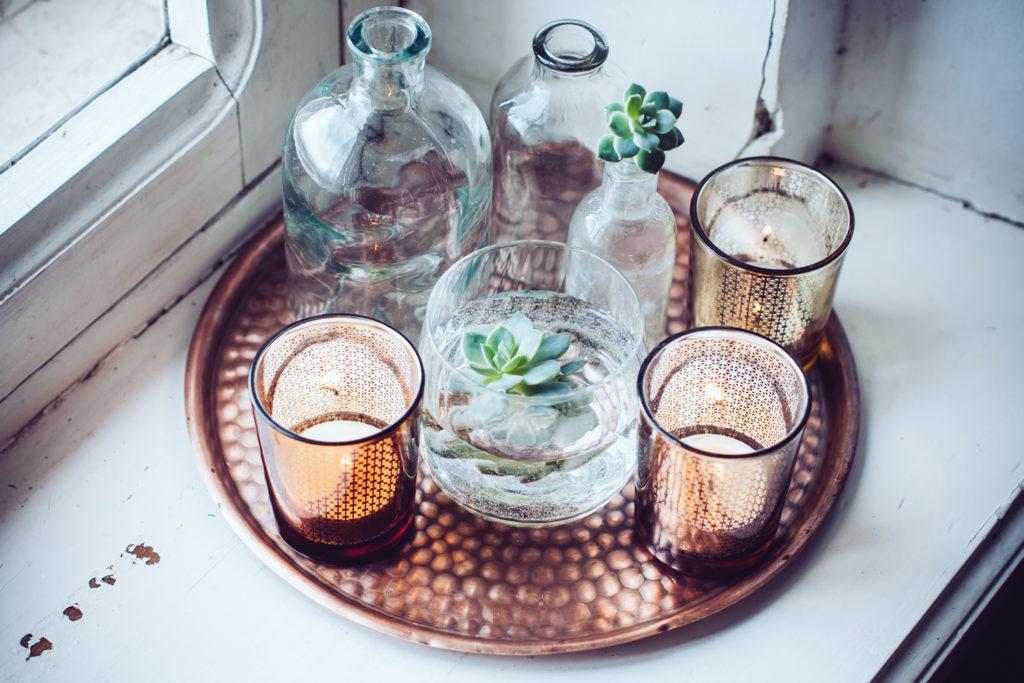 Kerzen, Vasen und Flaschen auf einem Tablett.