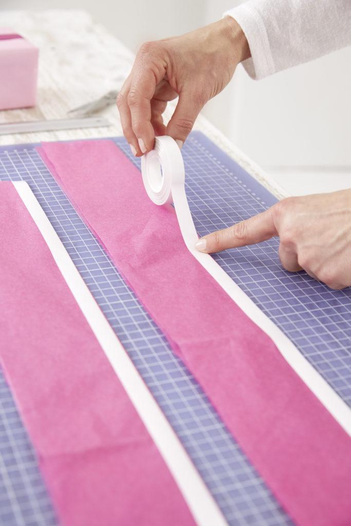 Papier wird mit Klebebband beklebt beim Pompons basteln.