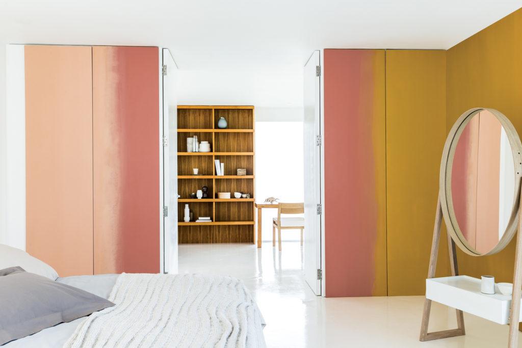Schlafzimmer in orange Tönen mit großem runden Standspiegel.