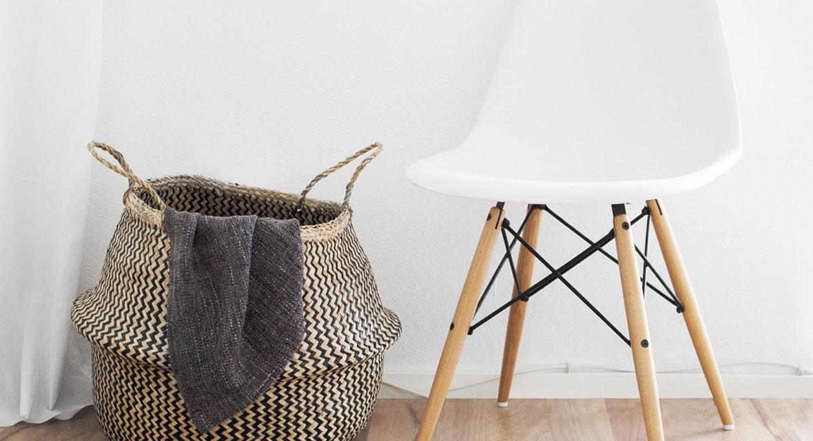 Weißer Stuhl steht neben Korb.