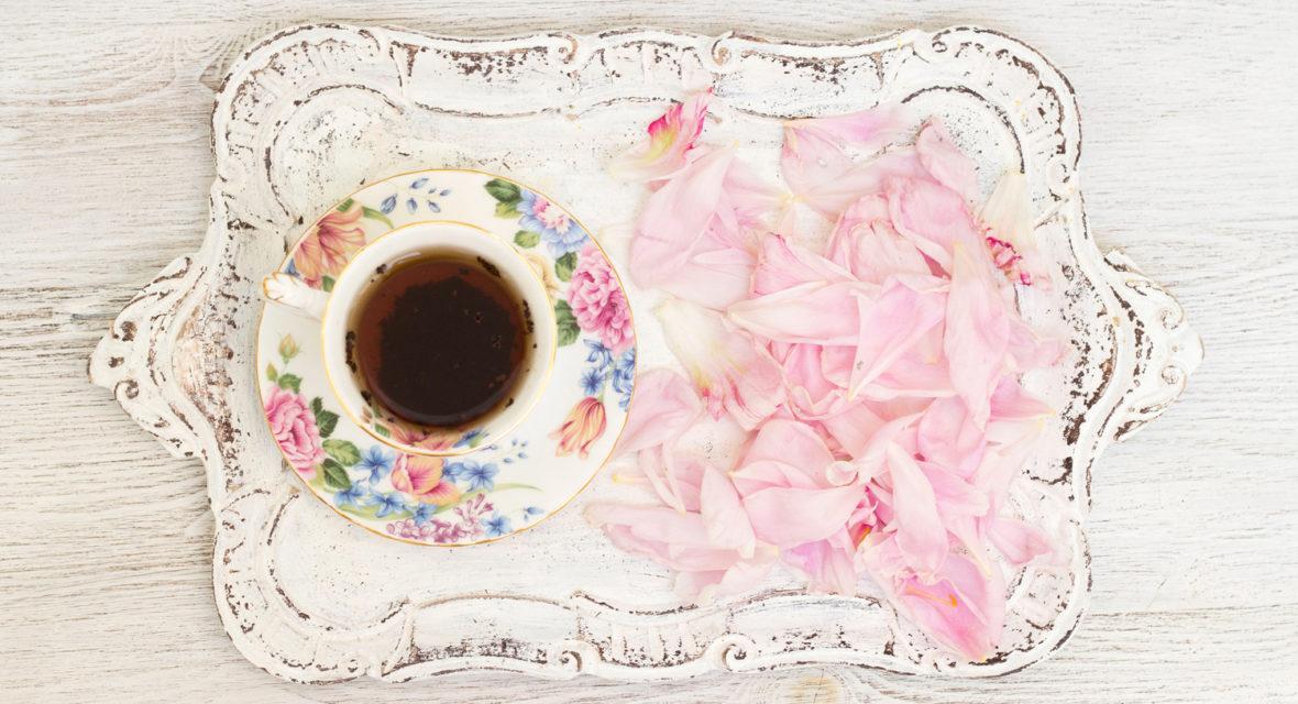 Auf einem Shabby Chic Tablett ist eine Tasse Tee und Rosenblätter.