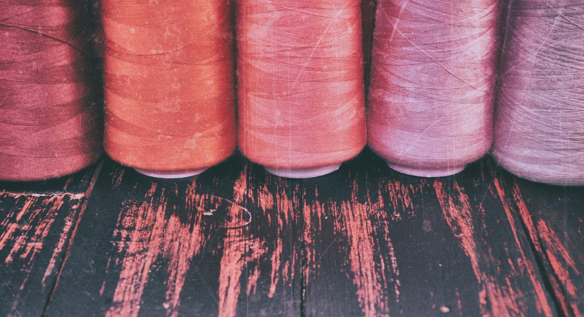 Pinke Fäden auf eienr Holz-Unterlage.