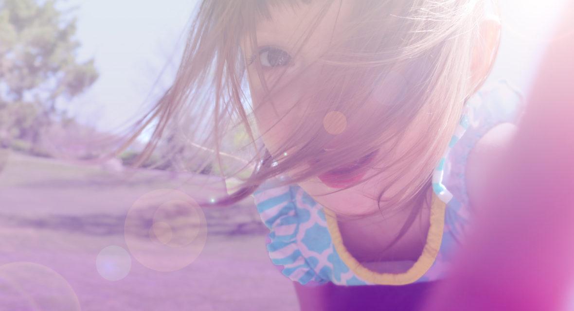 Mädchen spielt auf Wiese.
