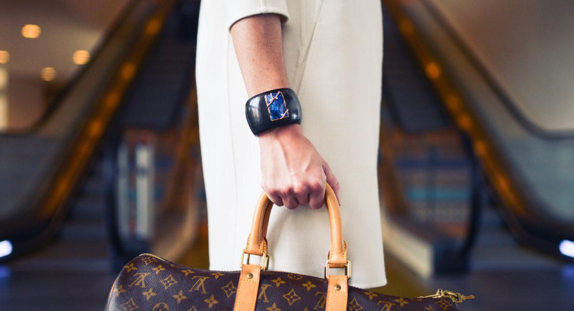 Frau mit Tasche steht vor Rolltreppe.