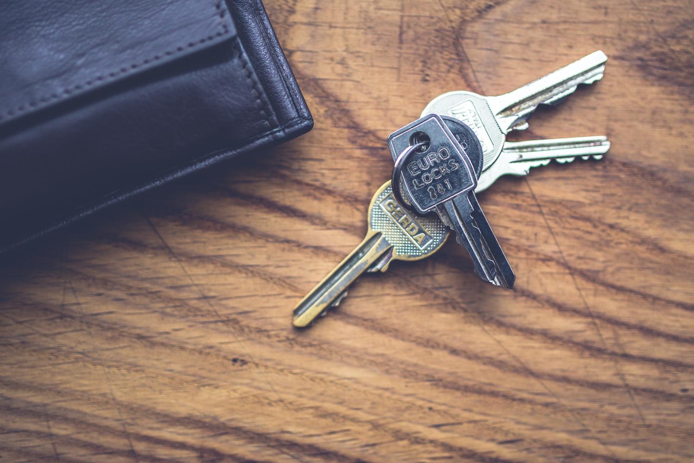 Schlüssel und Geldbeutel auf Tisch.