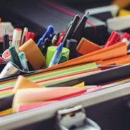 Papier, Stifte und Post its in einem Koffer.