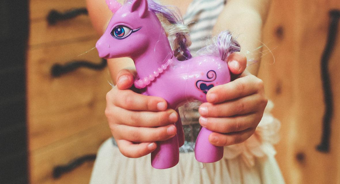 Kind hält Einhorn Figur.